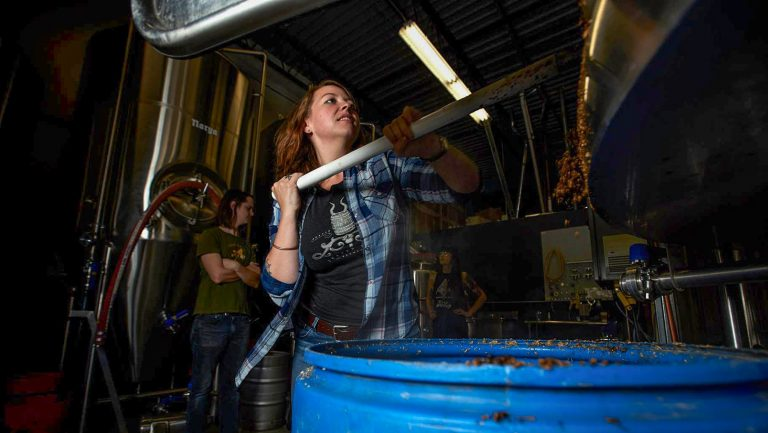 Averie Swanson of Jester King shoveling grains