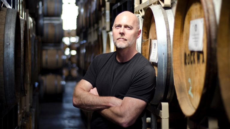 Master distiller Lance Winters poses in front of barrels filled with spirits at St. George