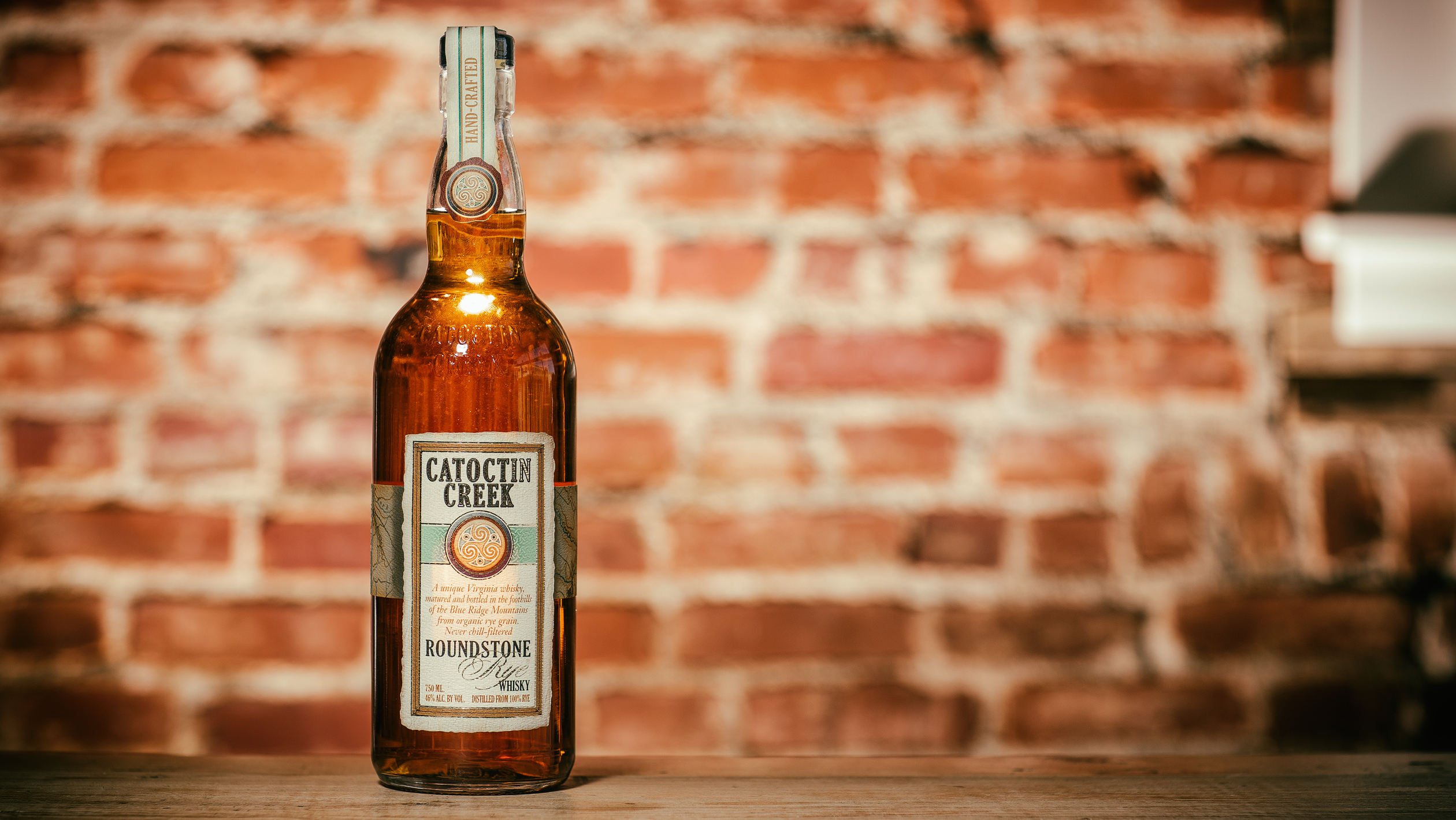 Bottle of whiskey in front of a brick wall