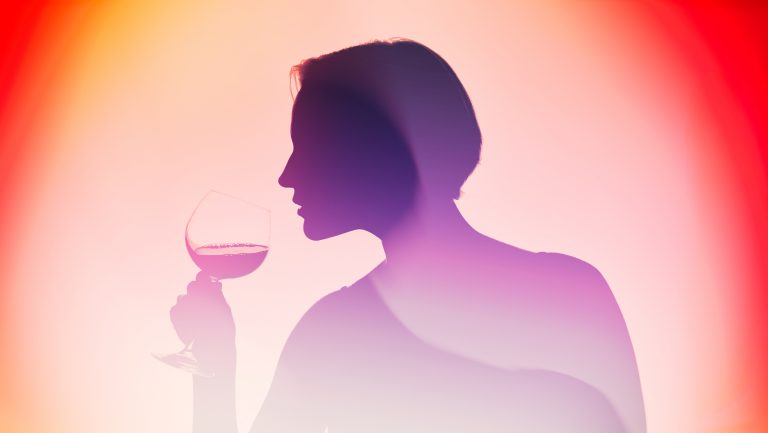 A silhouette of a woman smelling wine