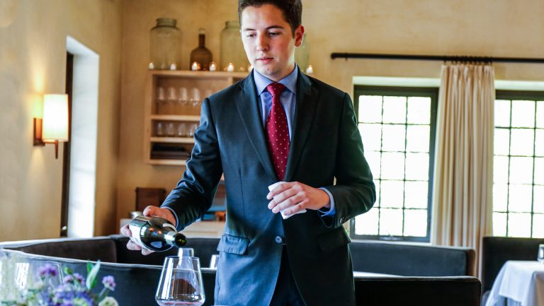 William Carroll pouring wine