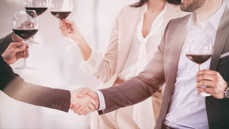people shaking hands and drinking wine