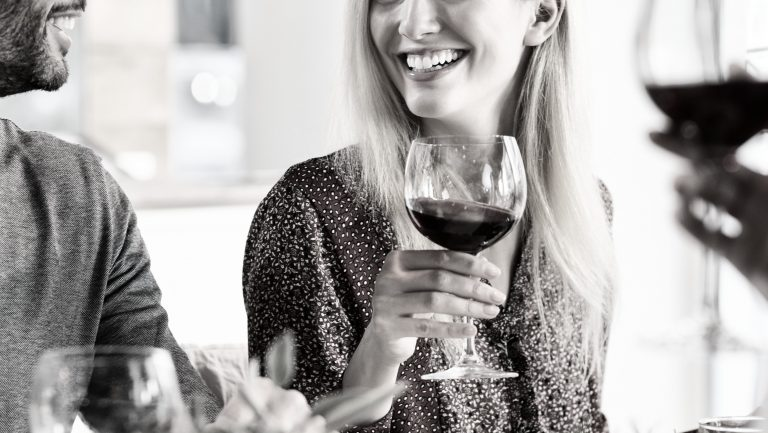 a_woman_smiling_holding_a_glass_of_wine